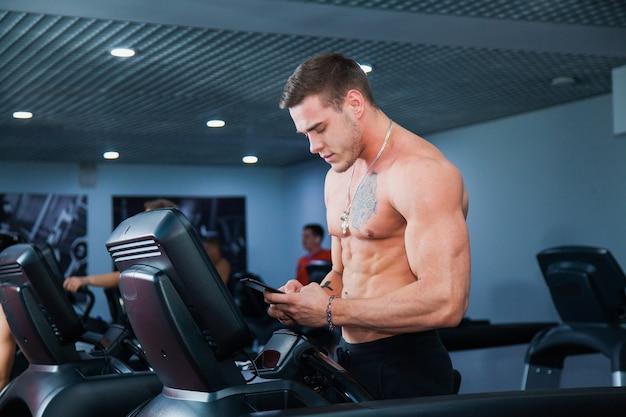 Jovem e bonito homem fazendo exercícios aeróbicos antes do treino