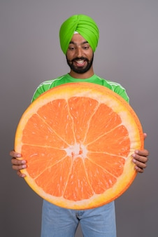 Jovem e bonito indiano sikh segurando uma grande fatia de laranja