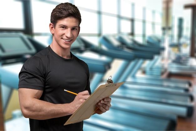 Jovem e bonito instrutor no centro de fitness