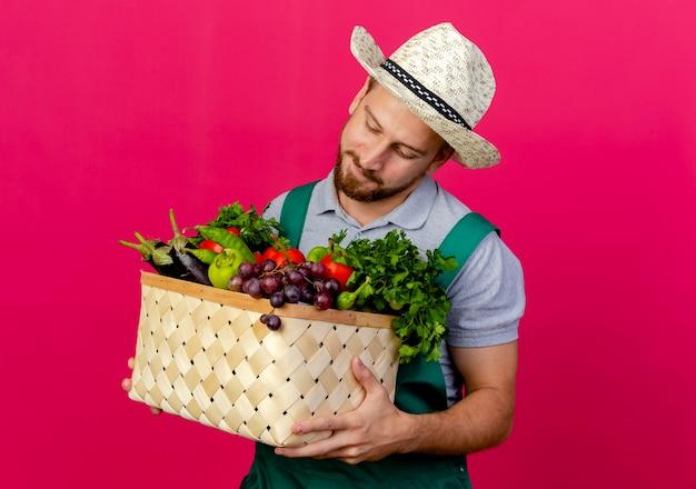 Jovem e bonito jardineiro eslavo de uniforme e chapéu segurando e olhando para uma cesta de legumes