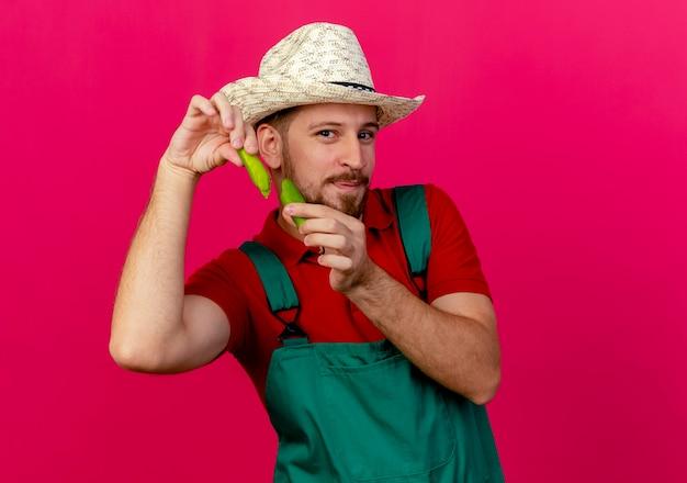 Jovem e bonito jardineiro eslavo de uniforme e chapéu segurando metades de pimenta olhando
