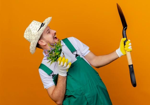 Jovem e bonito jardineiro eslavo de uniforme, impressionado, usando chapéu e luvas de jardinagem, segurando uma pá e um vaso de flores olhando a pá isolada