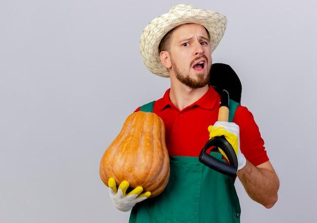 Jovem e bonito jardineiro eslavo de uniforme, impressionado, usando luvas de jardinagem e chapéu, segurando abóbora e pá parecendo isolado