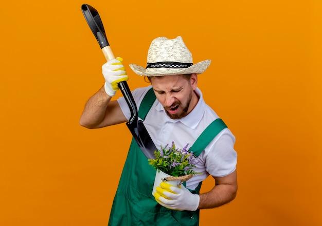 Jovem e bonito jardineiro eslavo de uniforme, irritado, usando chapéu e luvas de jardinagem, segurando uma pá e um vaso de flores espadeando flores em um vaso isolado