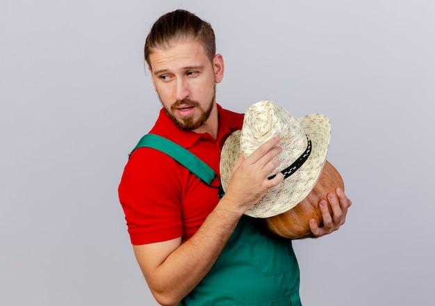 Jovem e bonito jardineiro eslavo de uniforme, segurando abóbora e chapéu olhando para o lado isolado