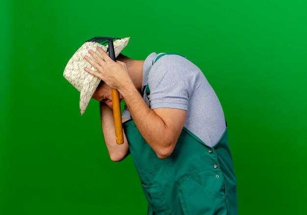 Jovem e bonito jardineiro eslavo estressado de uniforme e chapéu em pé na vista de perfil, segurando o ancinho e colocando as mãos nas orelhas