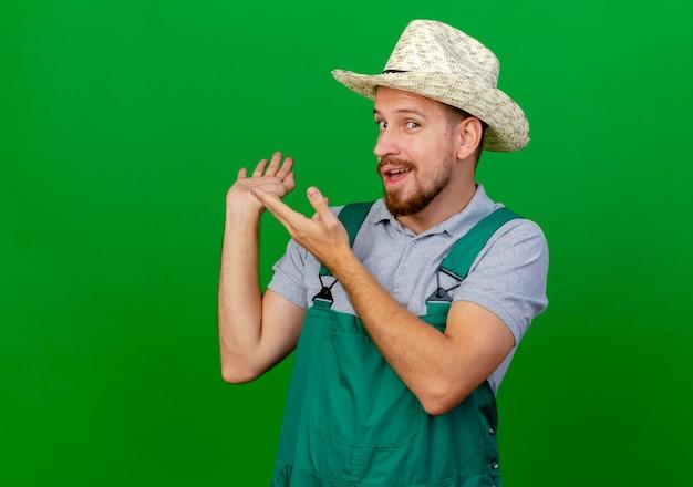 Jovem e bonito jardineiro eslavo impressionado de uniforme e chapéu olhando apontando com as mãos para trás