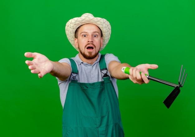Jovem e bonito jardineiro eslavo impressionado de uniforme e chapéu olhando estendendo as mãos segurando um ancinho isolado na parede verde
