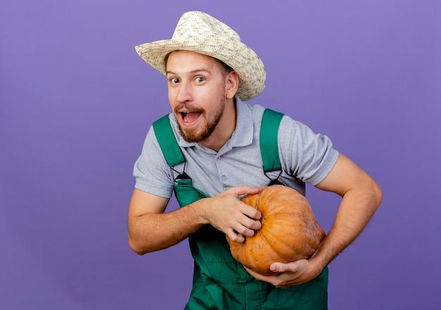 Jovem e bonito jardineiro eslavo impressionado de uniforme e chapéu segurando abóbora e parecendo isolado
