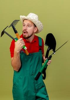 Jovem e bonito jardineiro eslavo impressionado de uniforme e chapéu segurando e olhando para ferramentas de jardineiro