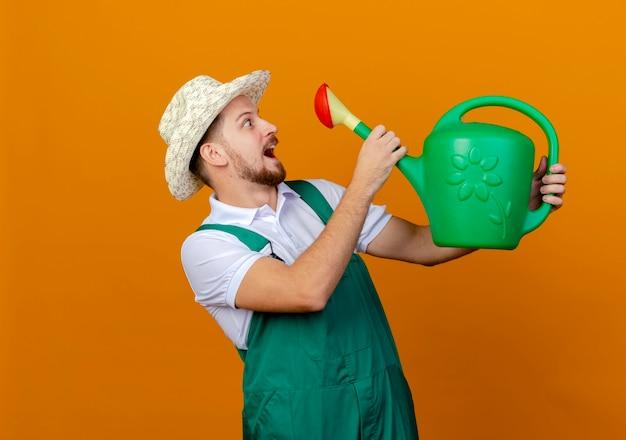 Jovem e bonito jardineiro eslavo impressionado de uniforme e chapéu segurando e olhando para um regador isolado