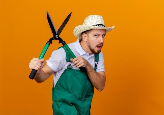 Jovem e bonito jardineiro eslavo impressionado de uniforme e chapéu segurando podadores e parecendo isolado