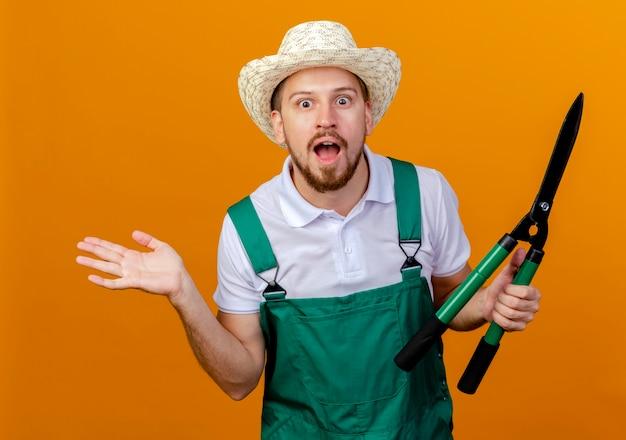 Jovem e bonito jardineiro eslavo impressionado de uniforme e chapéu segurando podadores, mostrando a mão vazia isolada na parede laranja