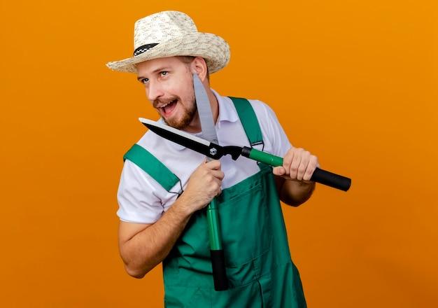 Jovem e bonito jardineiro eslavo impressionado de uniforme e chapéu segurando podadores olhando para o lado isolado