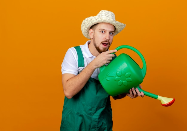 Jovem e bonito jardineiro eslavo impressionado de uniforme e chapéu segurando um regador, parecendo fingir que está regando isolado