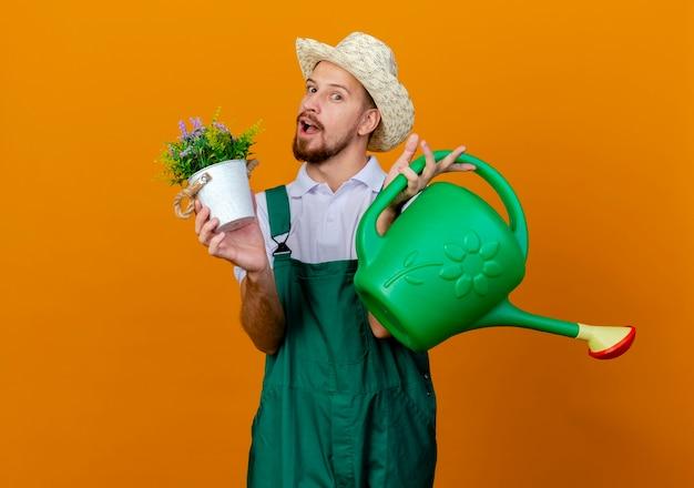 Jovem e bonito jardineiro eslavo impressionado de uniforme e chapéu segurando um vaso de flores e um regador, parecendo isolado