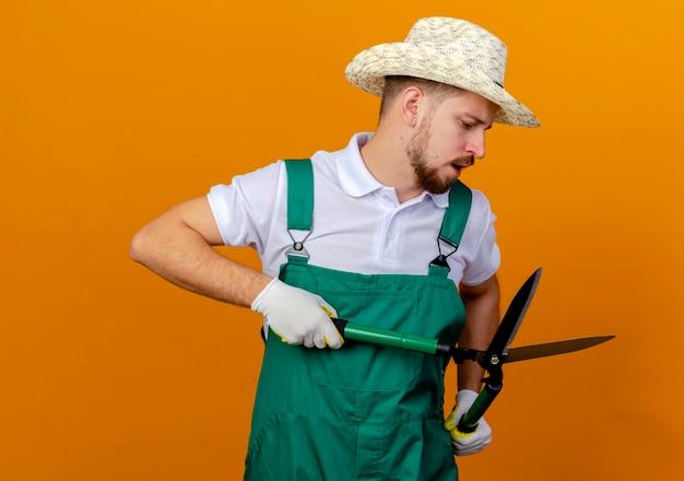 Jovem e bonito jardineiro eslavo impressionado de uniforme, usando chapéu e luvas de jardinagem, segurando e olhando para podadores isolados