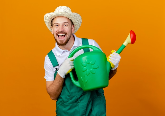 Jovem e bonito jardineiro eslavo impressionado de uniforme, usando chapéu e luvas de jardinagem, segurando um regador e parecendo isolado