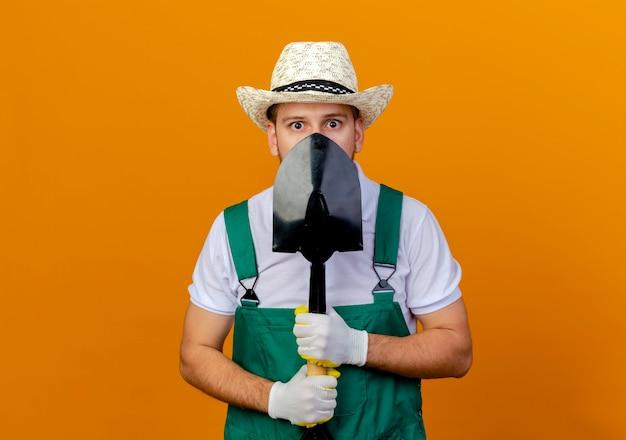 Jovem e bonito jardineiro eslavo impressionado de uniforme, usando chapéu e luvas de jardinagem, segurando uma pá, olhando isolado por trás
