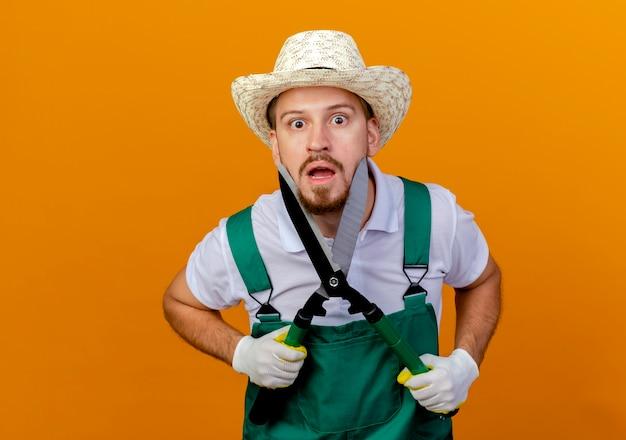 Jovem e bonito jardineiro eslavo impressionado de uniforme, usando chapéu e luvas de jardinagem, tocando o rosto com podadores parecendo isolados