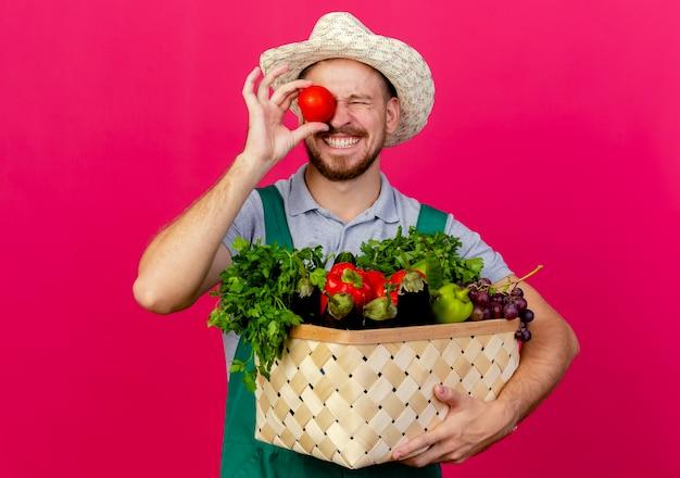 Jovem e bonito jardineiro eslavo sorridente de uniforme e chapéu segurando uma cesta de vegetais segurando um tomate no olho com os olhos fechados, isolado na parede carmesim