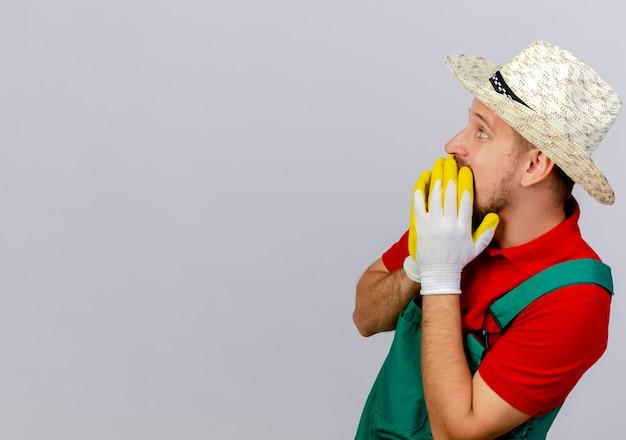 Jovem e bonito jardineiro eslavo surpreso de uniforme e chapéu com luvas de jardineiro em pé na vista de perfil, mantendo as mãos na boca, parecendo bem isoladas