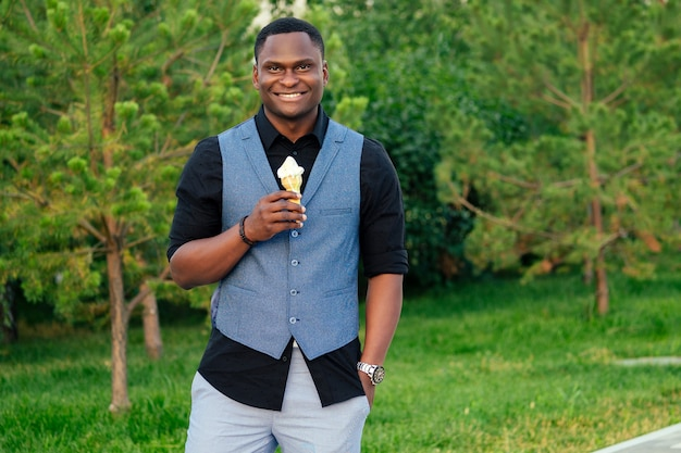 Jovem e bonito modelo elegante homem afro-americano em um elegante terno azul em um parque de verão inteligente latino hispânico empresário negro comendo sorvete doce em um chifre de waffle