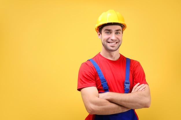 Jovem e bonito trabalhador na parede amarela