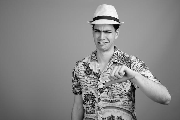 Jovem e bonito turista persa vestindo camisa havaiana e chapéu pronto para as férias em preto e branco