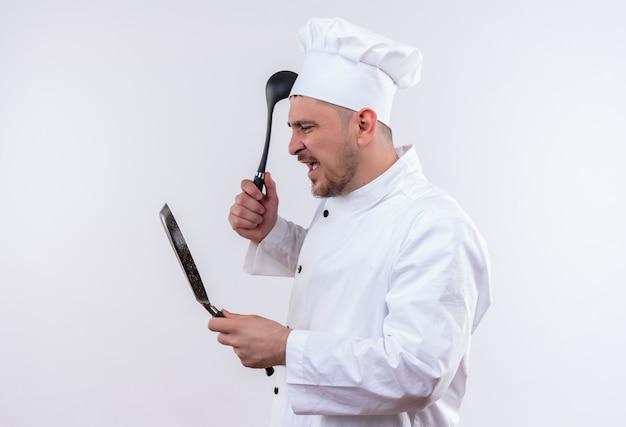 Jovem e bravo cozinheiro bonito em uniforme de chef segurando uma frigideira e uma concha olhando para a frigideira na parede branca isolada