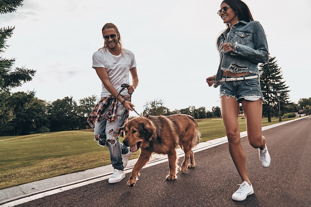 Jovem e cheio de energia. comprimento total de um lindo casal jovem correndo com seu cachorro enquanto passa o tempo ao ar livre
