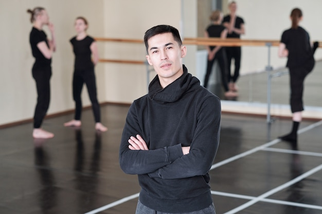 Jovem e confiante instrutora de curso de balé moderno cruzando os braços no peito enquanto posa