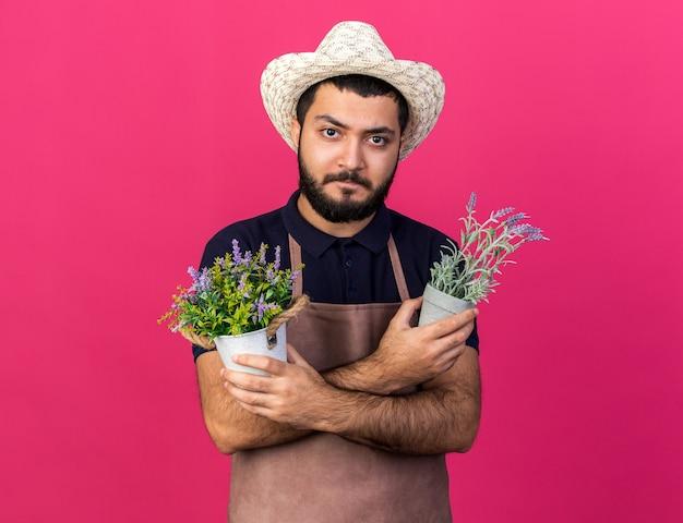 Jovem e confiante jardineiro caucasiano com chapéu de jardinagem e segurando vasos de flores, cruzando os braços isolados na parede rosa com espaço de cópia