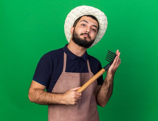 Jovem e confiante jardineiro caucasiano com chapéu de jardinagem, segurando o ancinho e parecendo isolado em uma parede verde com espaço de cópia