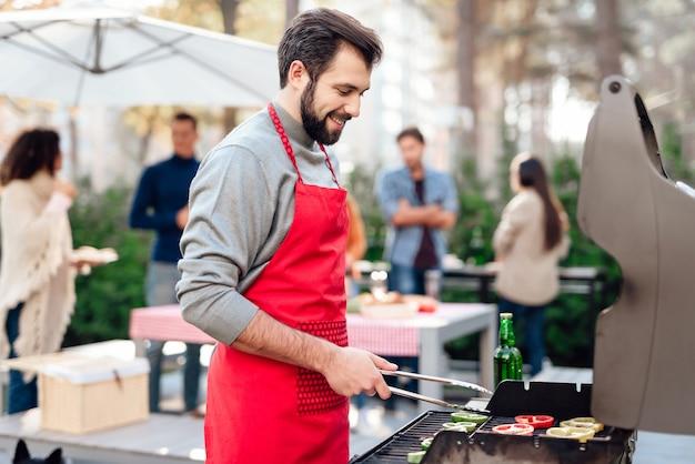 Jovem é cozinhar comida de churrasco.