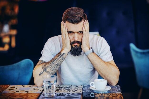 Jovem e desesperado barbudo tatuado musculoso bonito hippie de mãos dadas