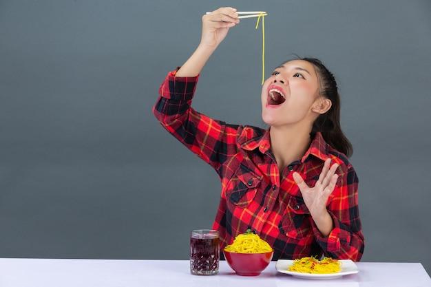Jovem é desfrutar de comer espaguete em casa