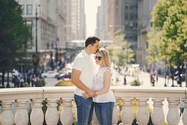 Jovem e elegante casal de amantes em t-shirts brancas e jeans azul andando em uma cidade grande