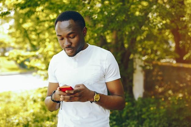 Jovem e elegante menino de pele escura em uma camiseta branca fica em um parque de verão ensolarado