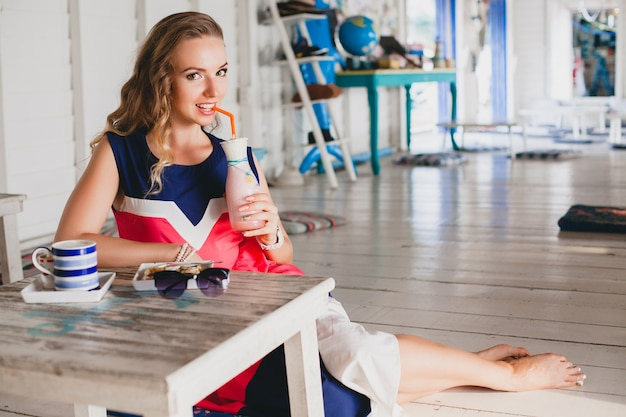 Jovem e elegante mulher bonita no café do mar, bebendo batido de coquetel, óculos de sol, glamour, estilo resort, roupa da moda, sorrindo, vestido de cores marinhas