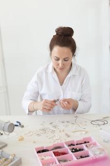 Jovem e entusiasmada mulher caucasiana fazendo belas bijuterias exclusivas enquanto está sentado