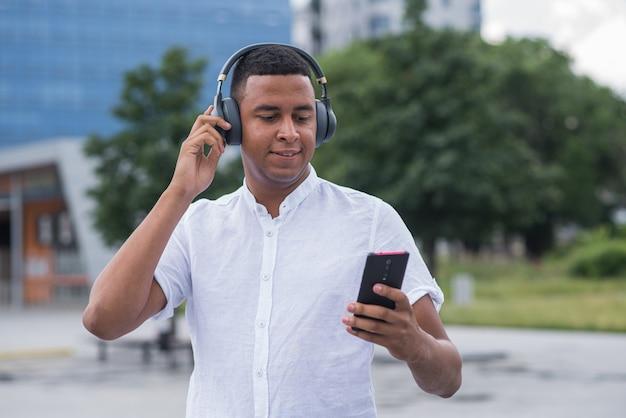 Jovem e feliz afro-americano ouvindo música com fones de ouvido e usando o smartphone