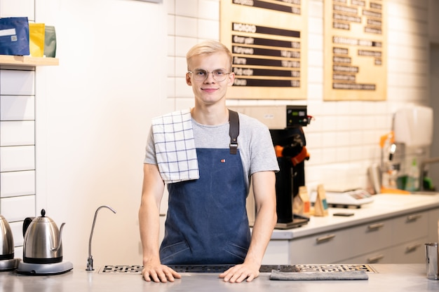 Jovem e feliz barista de sucesso em roupas de trabalho, aguardando no local de trabalho em um café enquanto espera por novos convidados