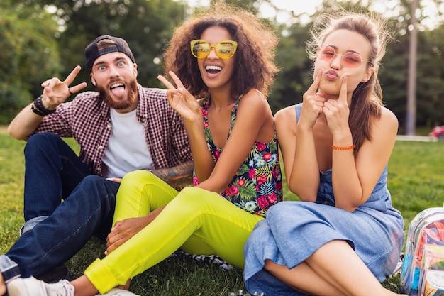 Jovem e feliz companhia de amigos sentados no parque, brincando com caras malucas e engraçadas, homens e mulheres se divertindo juntos