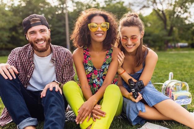 Jovem e feliz companhia de amigos sentados no parque, homens e mulheres se divertindo juntos, viajando com a câmera, conversando, sorrindo