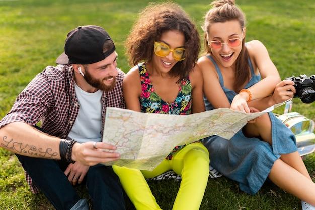 Jovem e feliz companhia de amigos sentados no parque, viajando, olhando no mapa turístico, homens e mulheres se divertindo juntos