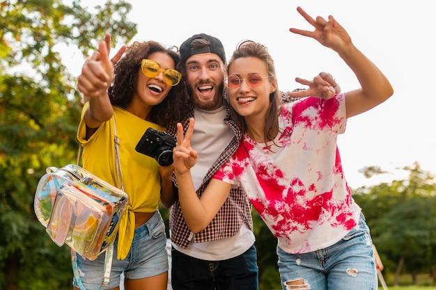 Jovem e feliz companhia de amigos sorridentes e emocionais caminhando no parque com a câmera fotográfica, homens e mulheres se divertindo juntos