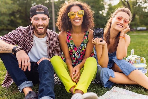 Jovem e feliz companhia de amigos sorridentes sentados no parque, homens e mulheres se divertindo juntos, viajando com a câmera