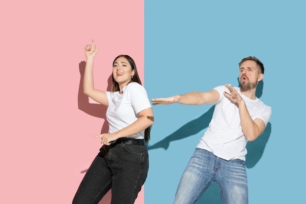 Jovem e feliz homem e mulher em roupas casuais na parede bicolor rosa, azul, dançando