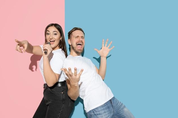 Jovem e feliz homem e mulher em roupas casuais na parede bicolor rosa e azul